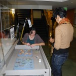 Rene Young works and student Cherkea Howery arrange artifacts in case drawers.