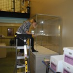 Lisa Newble adjusts the height of the shelves in one of the cases.