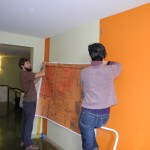 Rene Yung and preparator Colin hang a floor-to-ceiling 1884 map of the Market Street Chinatown.